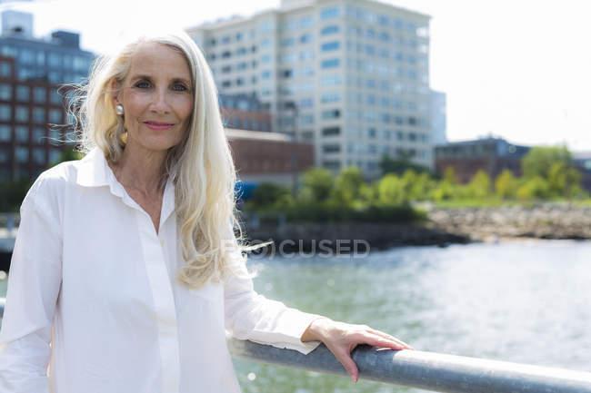 Retrato de mulher idosa em pé perto de corrimão do rio — Fotografia de Stock