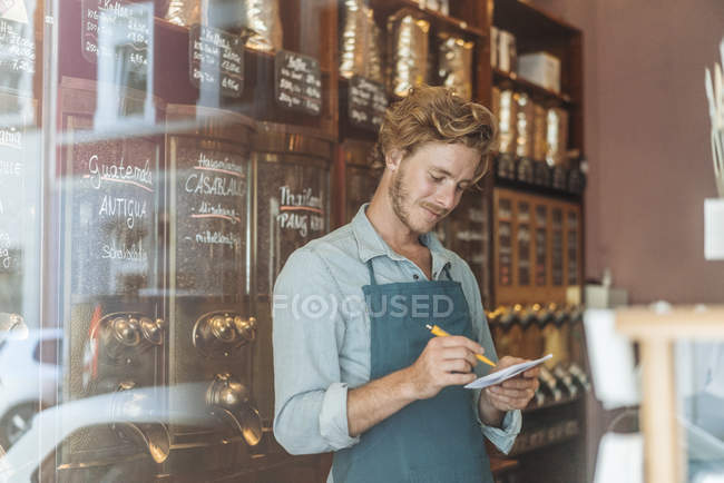 Coffee roaster taking notes in shop — Stock Photo