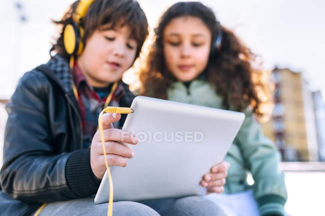 Двое детей слушают музыку с планшетом и наушниками — стоковое фото