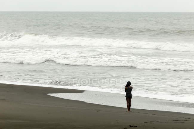 Indonesia, Java, woman walking at ocean coastline — Stock Photo