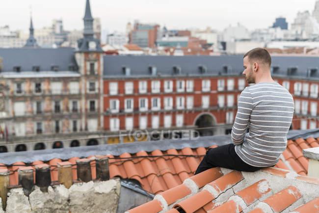 Hombre sentado en la terraza disfrutando de las vistas del paisaje urbano de Madrid, España - foto de stock