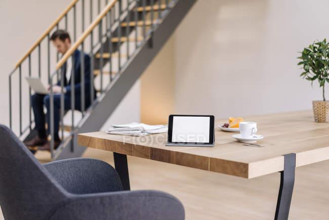 Офісний стіл з планшетних і робочих бізнесмен на тлі — стокове фото