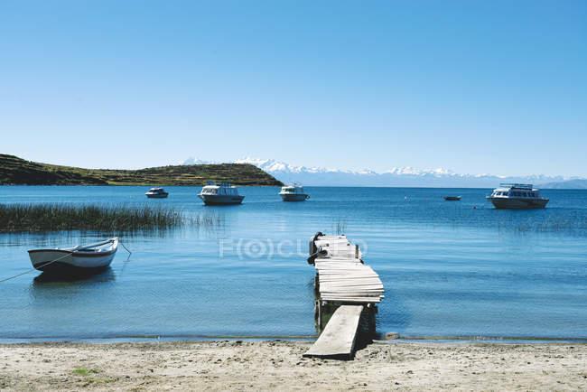 Muelle y barcos con los Andes en el fondo, Isla del sol, Lago Titicaca, Bolivia - foto de stock
