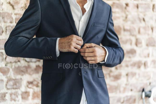 Крупный план куртки бизнесмена перед кирпичной стеной — стоковое фото