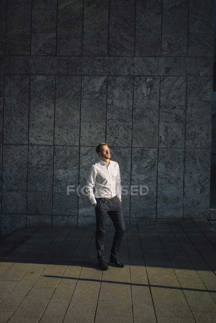 Portrait d'un homme d'affaires debout près d'un mur — Photo de stock