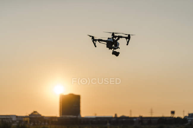 One quadcopter with camera flying at sunset — Stock Photo