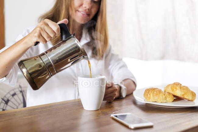 Donna versando il caffè in tazza a tavola colazione — Foto stock
