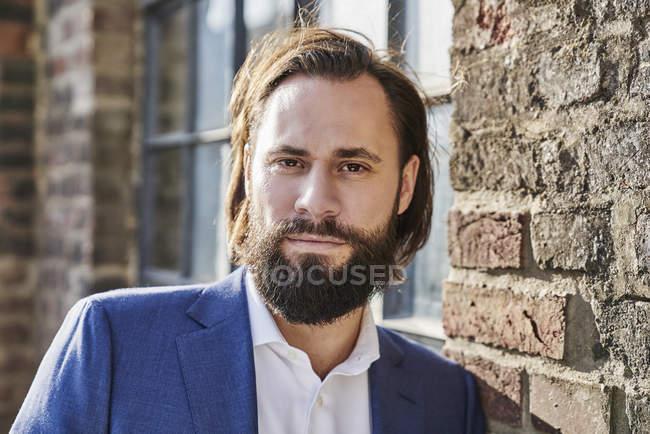Geschäftsmann steht vor Backsteingebäude — Stockfoto