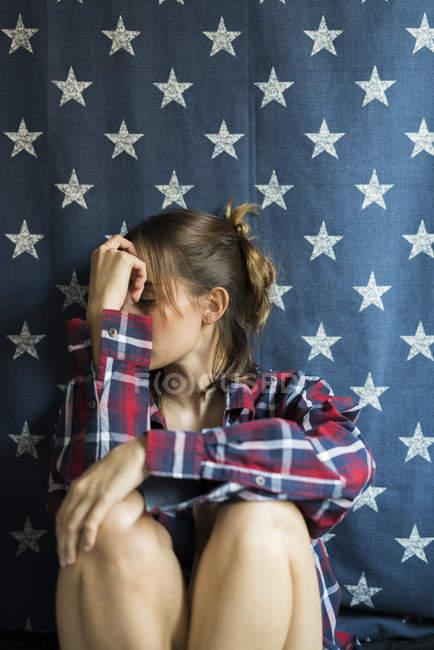 Junge Frau sitzt zu Hause und verdeckt Gesicht mit der Hand — Stockfoto