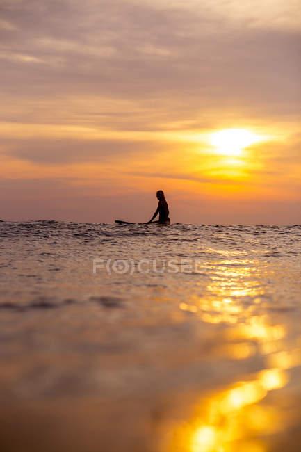 Surfeuse dans l'océan au coucher du soleil avec un ciel romantique — Photo de stock