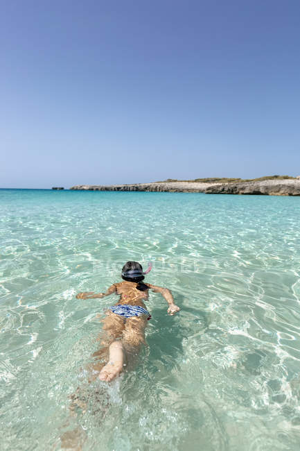 Spain, Menorca, Talaier Beach, girl snorkeling in turquoise water — Stock Photo