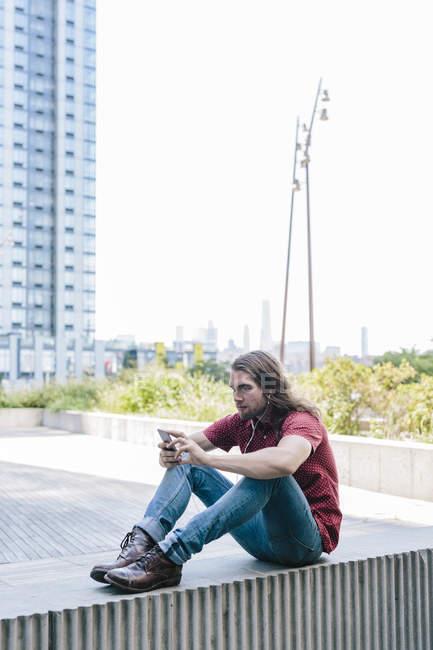 Портрет мужчины среднего возраста, сидящего на стене с мобильным телефоном — стоковое фото