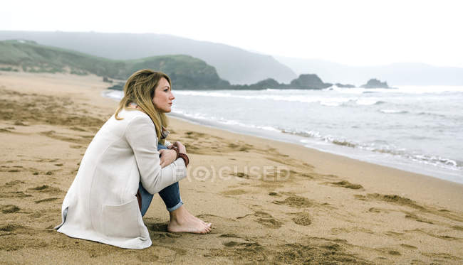 Spain, Asturias, Lonely woman barefoot looking the sea sitting in the beach sand — Stock Photo