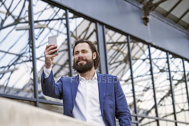 Businessman taking selfie with smartphone — Stock Photo