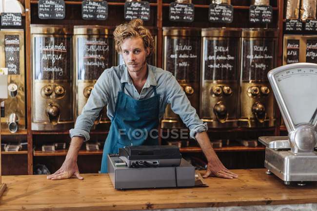Portrait of coffee roaster standing at counter in shop — Stock Photo