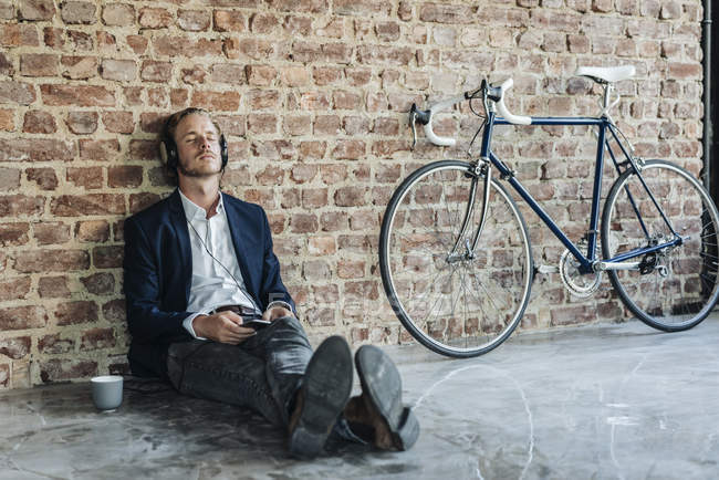 Relaxed businessman with headphones leaning against brick wall — Stock Photo