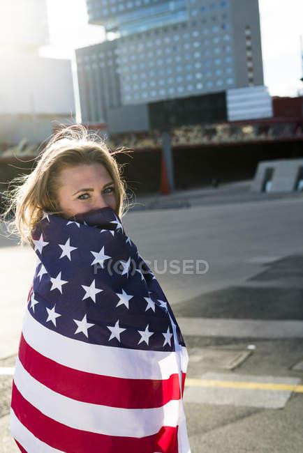 Mädchen in amerikanische Flagge gehüllt auf Straße und blickt in Kamera — Stockfoto