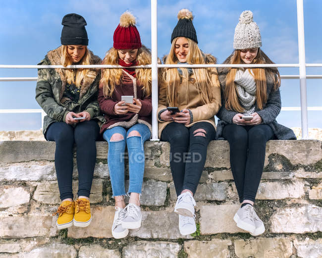 Four young women texting with smartphones — Stock Photo