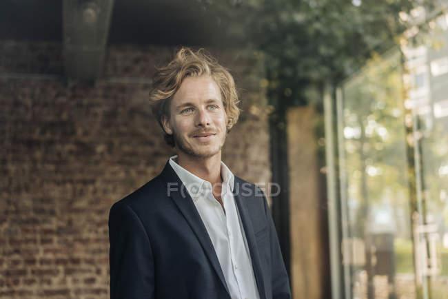 Portrait of smiling businessman looking sideways behind windowpane — Stock Photo