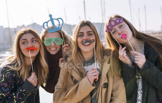 Quattro giovani donne goofing intorno con un falso baffi e corone — Foto stock
