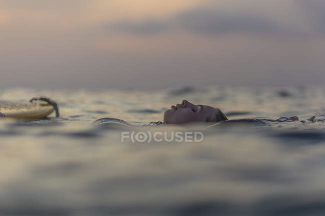 Relaxed female surfer floating in the ocean at sunset — Stock Photo