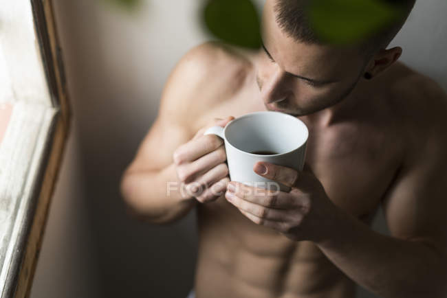 Jovem peito nu com xícara de café, vista elevada — Fotografia de Stock
