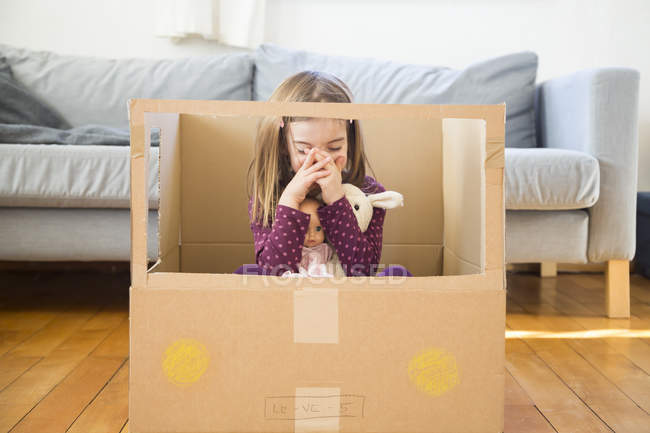 Девушка с куклой сидит дома в картонном вагоне — стоковое фото