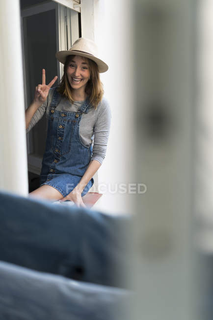 Girl in hat showing peace sign sitting on windo wsill — Stock Photo
