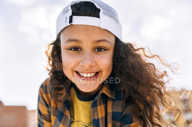 Cute little girl in baseball cap looking at camera — brown hair ... c2de2291bec