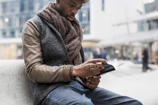 Young man sitting on bench reading a book — Stock Photo
