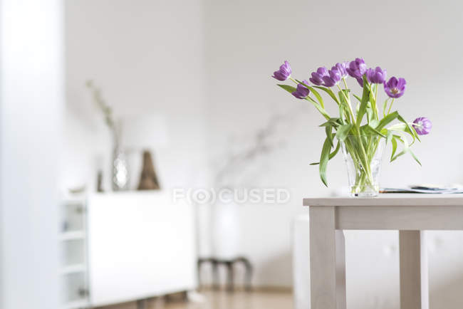 Violet tulips in vase on wooden table — Stock Photo