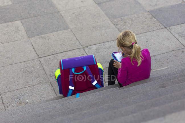Costas da menina com bolsa escola, sentado na escada fazendo lição de casa — Fotografia de Stock