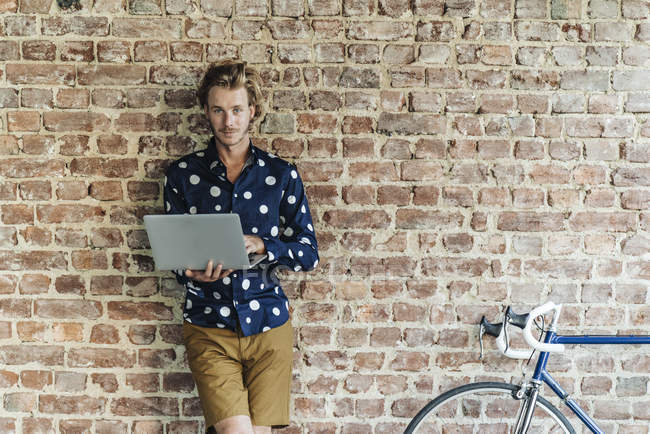 Portrait of funky smiling man standing with laptop in front of brick wall — Stock Photo