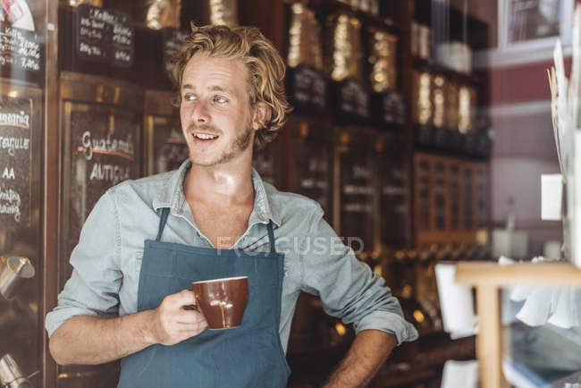 Smiling coffee roaster holding cup of coffee in shop — Stock Photo