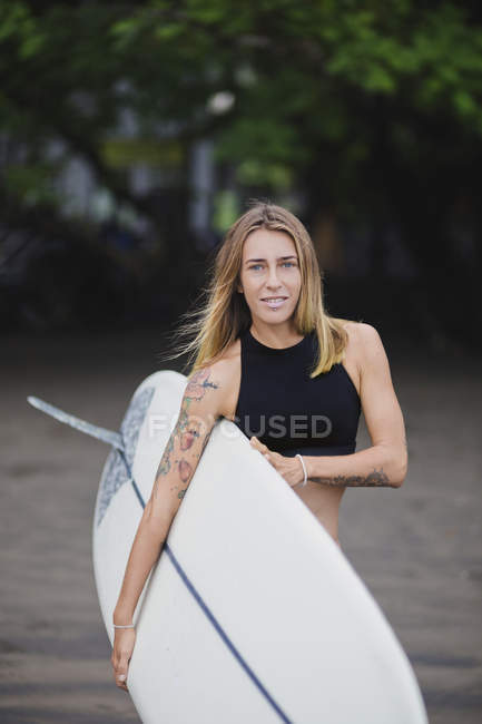 Portrait of smiling woman carrying surfboard on the beach — Stock Photo