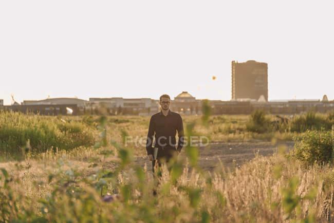 Porträt eines Geschäftsmannes, der mit Laptop im Feld steht — Stockfoto