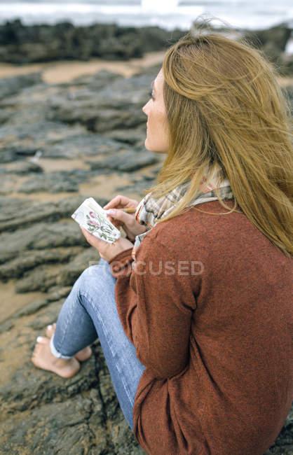 Femme avec ordinateur portable assis sur des rochers sur la plage en hiver — Photo de stock