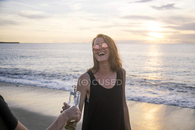 Indonesia, Bali, happy woman clinking beer bottles with friend on the beach at sunset — Stock Photo