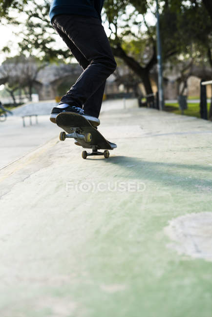 Skater boy tricking on skateboard, low section view — Stock Photo