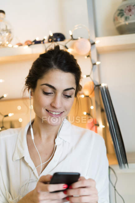Portrait of smiling woman listening music with earphones and smartphone — Stock Photo