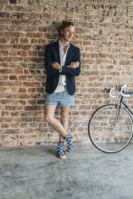 Funky Businessman standing in front of brick wall wearing jacket and underwear — Stock Photo