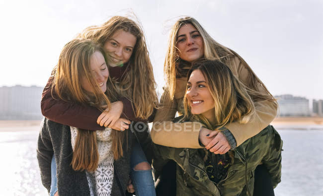 Four young women having fun on beach — Stock Photo