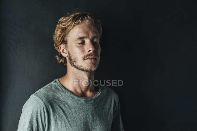 Portrait of blond man standing with closed eyes on black background — Stock Photo