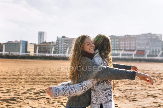 Gijn, Asturias, Spain, two good friends giving each other a hug on the beach — Stock Photo