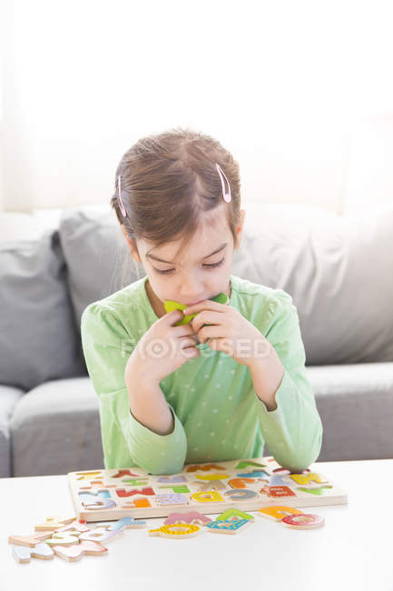 Menina aprendendo alfabeto com letras de madeira em casa — Fotografia de Stock