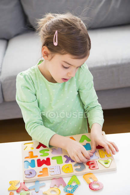 Little girl learning alphabet with wooden letters at home — Stock Photo