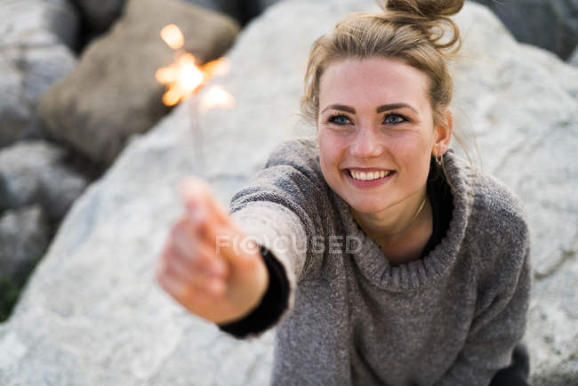 Overhead view of girl with burning sparkler — Stock Photo