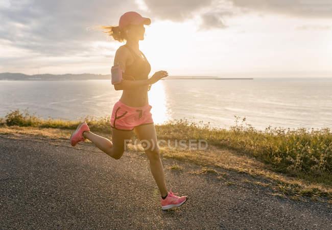 Mujer corriendo en la costa del mar - foto de stock