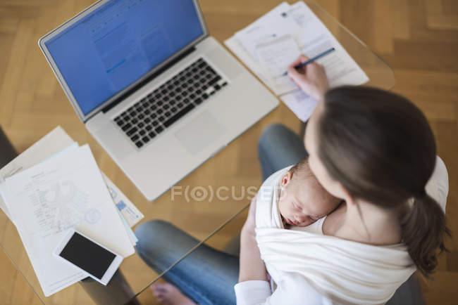 Erhöhten Blick auf Freelancer-Mutter mit Baby im Tragetuch in Heimarbeit Büro — Stockfoto