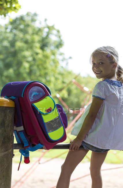 Menina a sorrir com saco de escola, sentado no bar alta de um playground — Fotografia de Stock